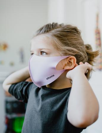 Little girl putting on a mask.