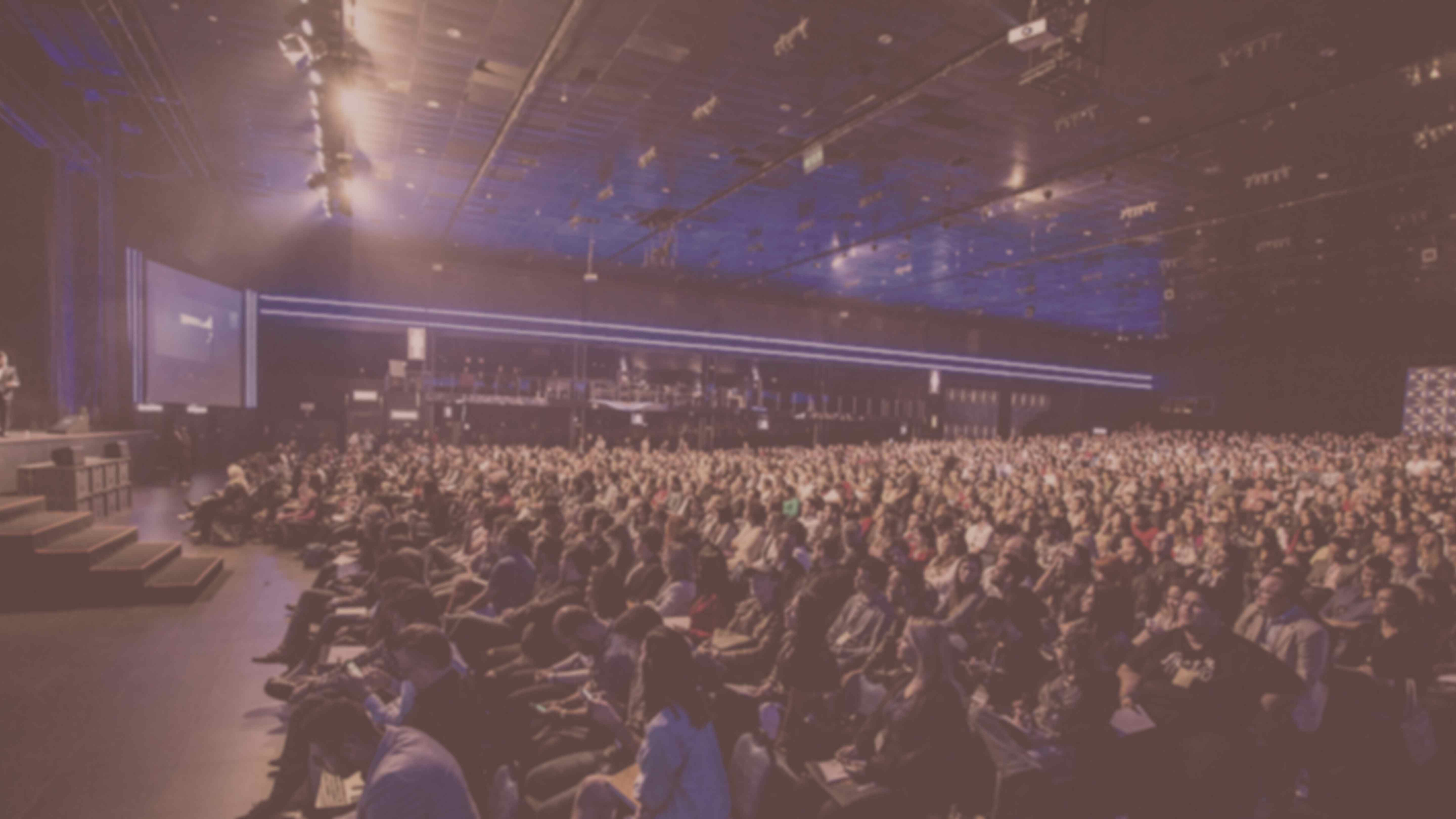 Audience of hundreds of people facing the stage at a conference