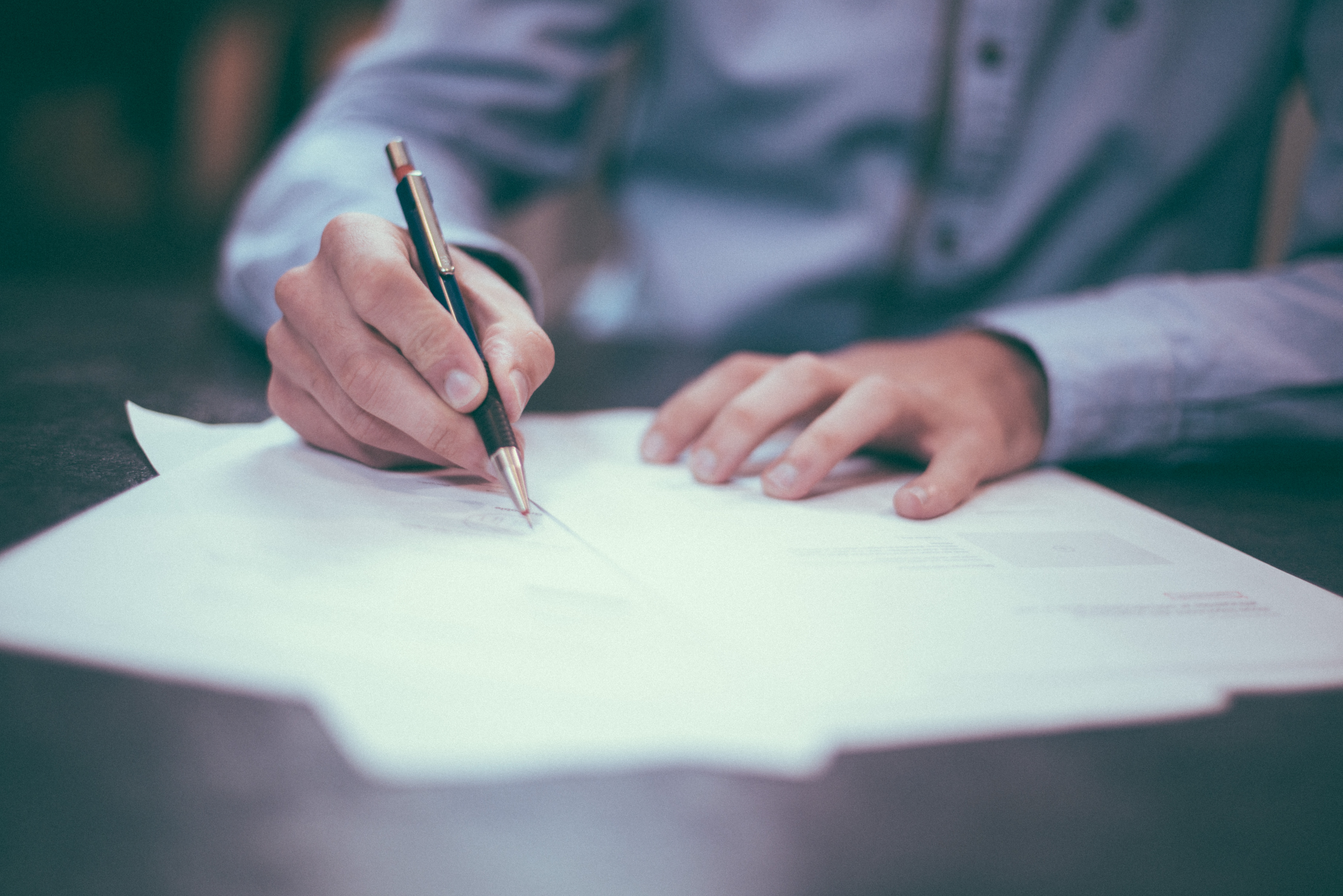 Man in shirt writing on papers with pen