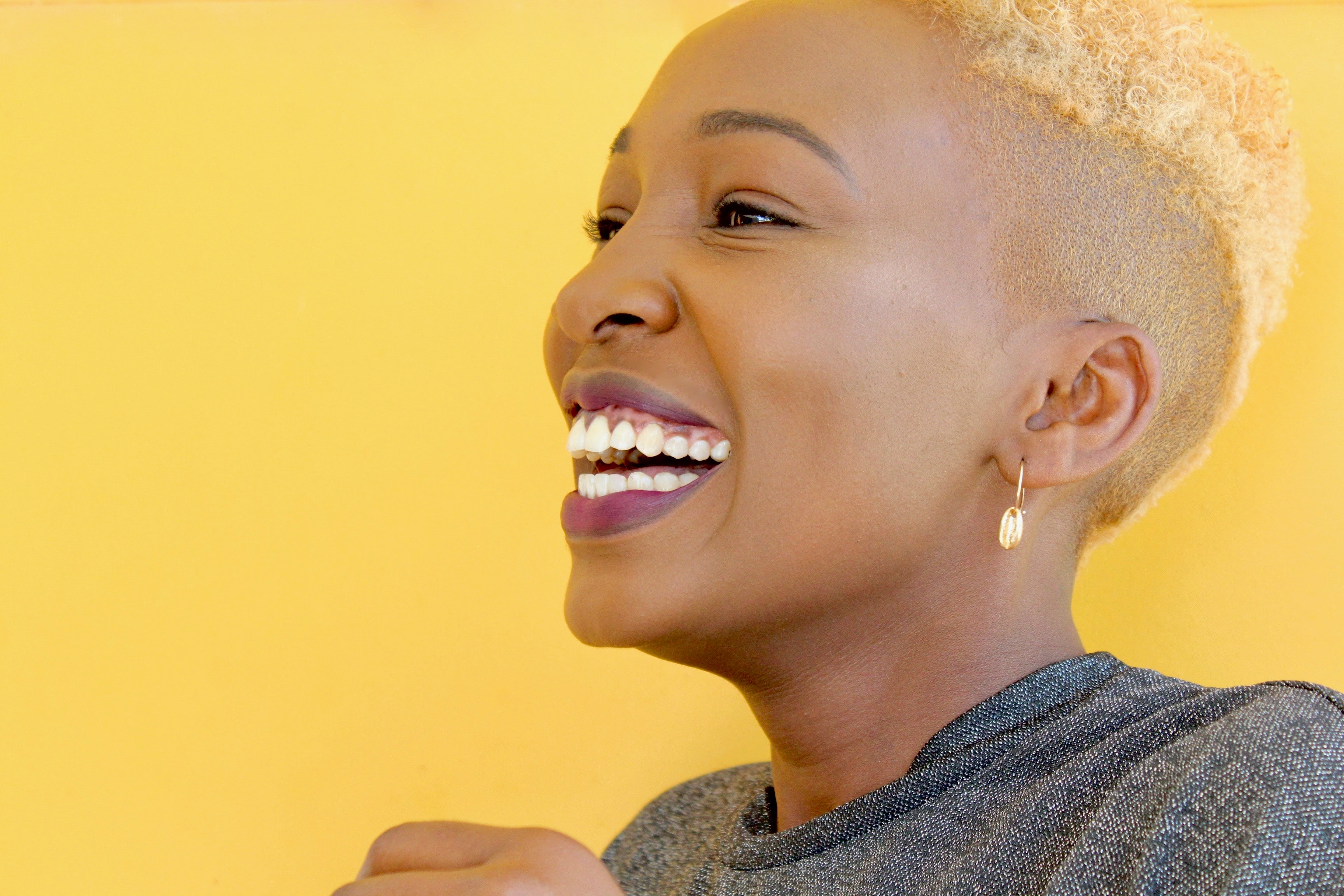 Close up of black women laughing with yellow background