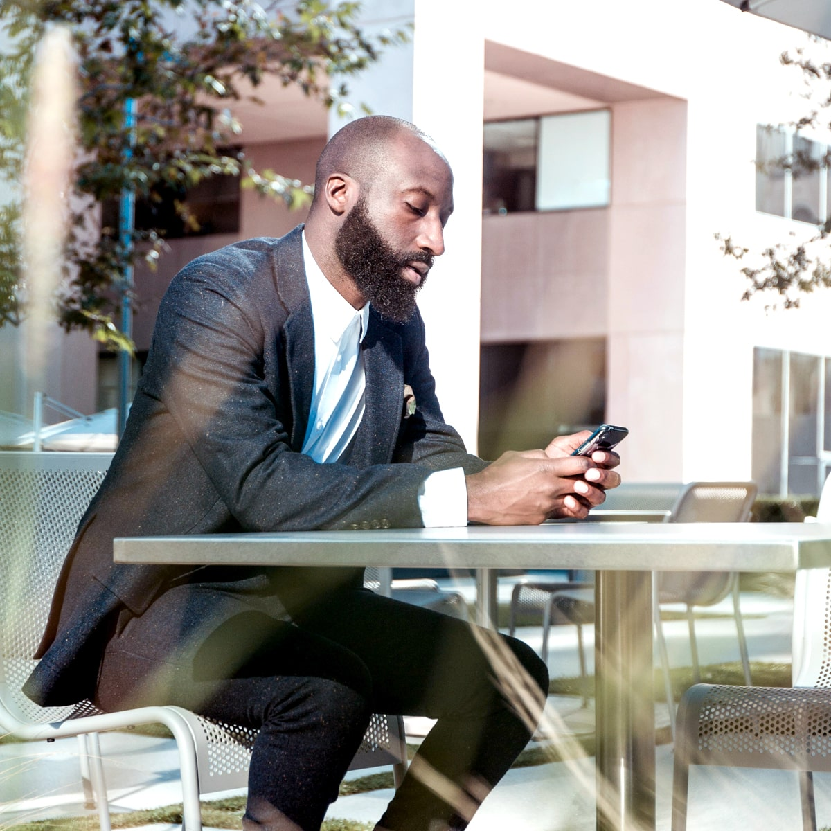 Black man in suit viewing the phone in his had while sitting on a table outside.