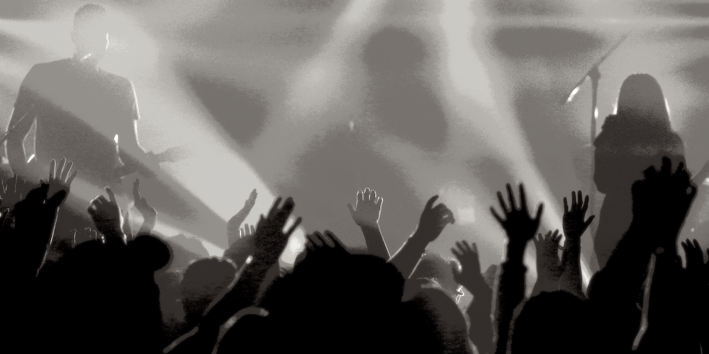 An audience at a rock concert with raised hands