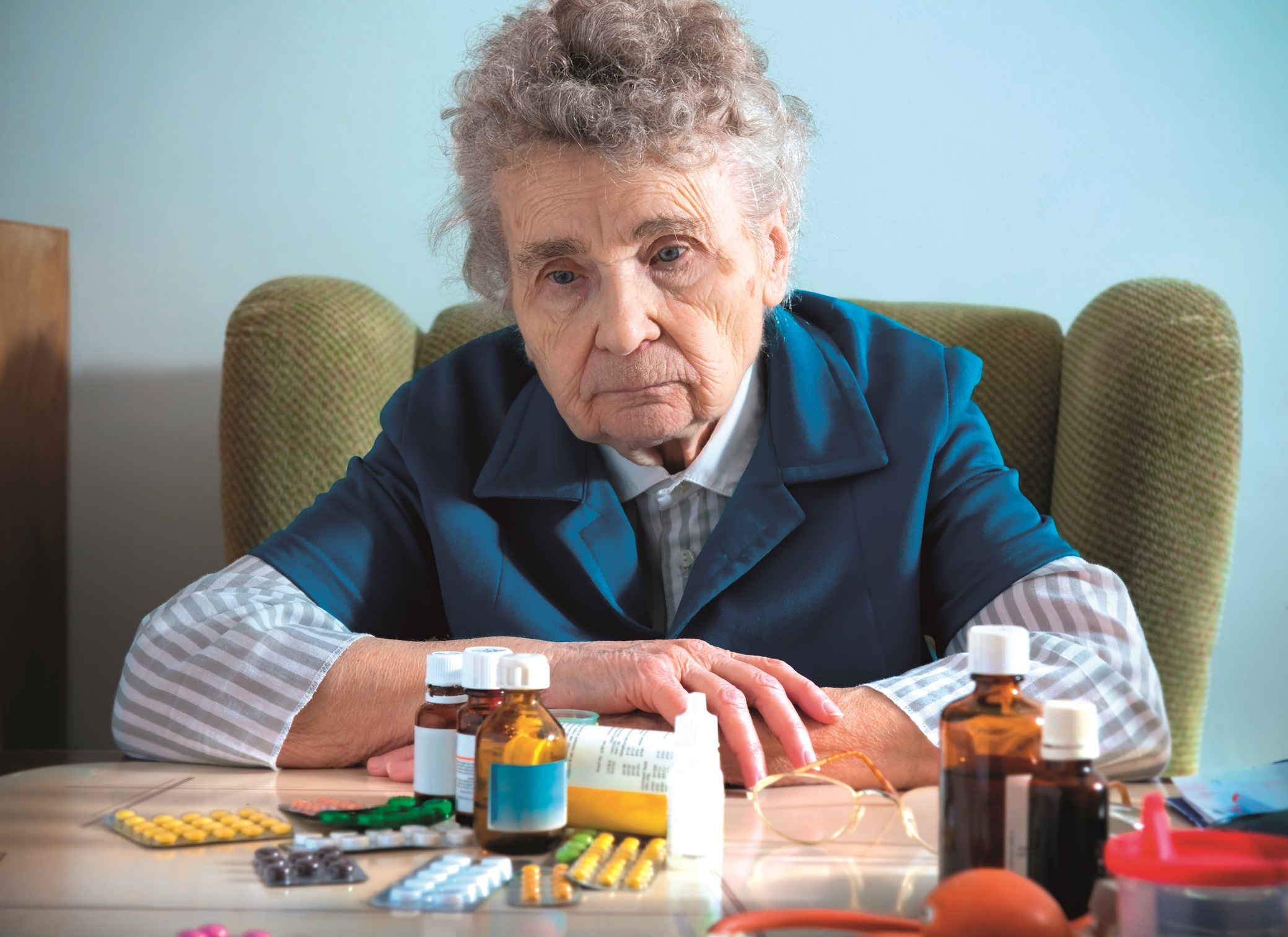 An elderly women trying to mange her many medications, by herself