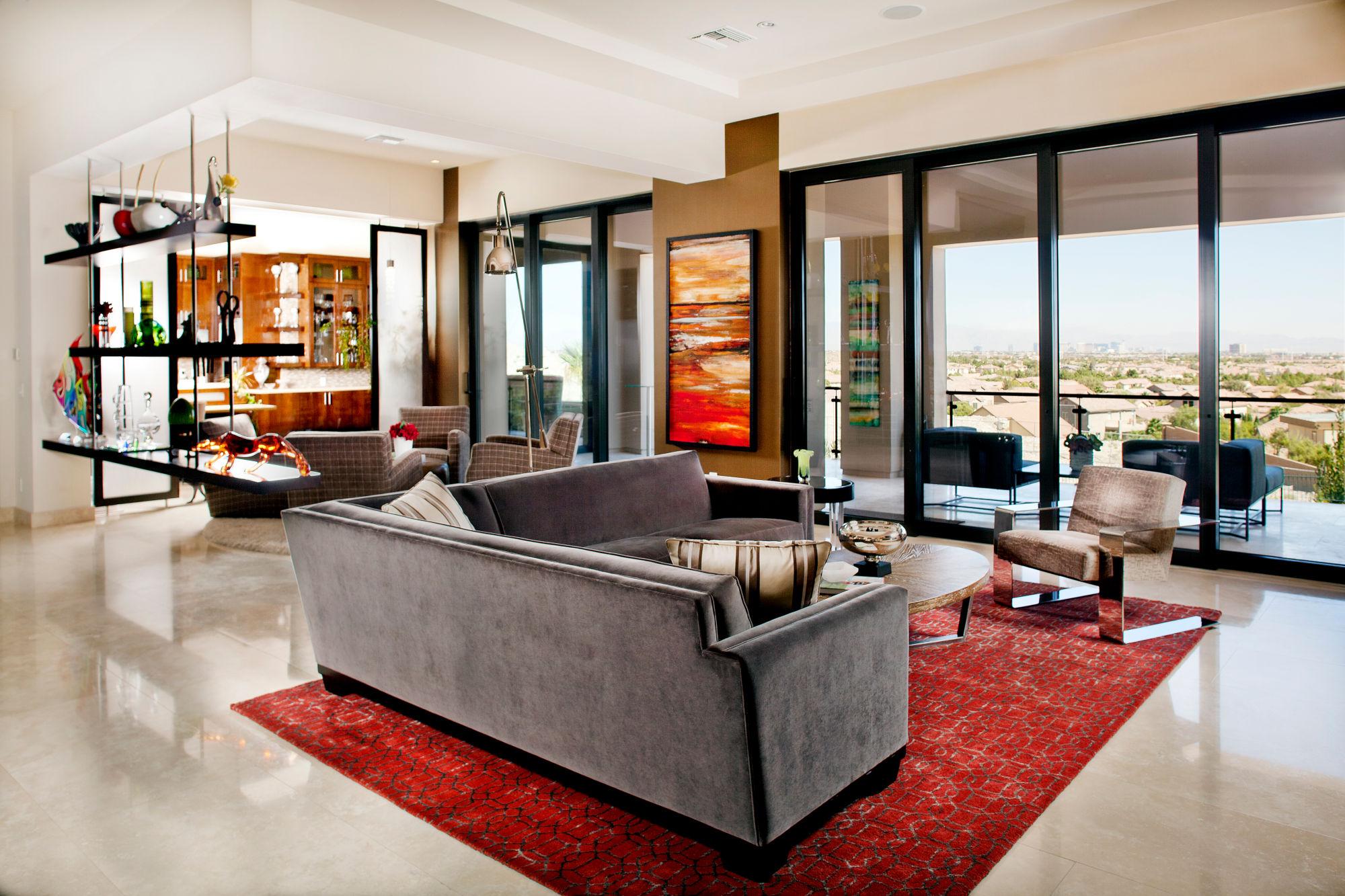 Family room with modern furnishings, large sliders, orange silk area rug, gray velvet sectional.