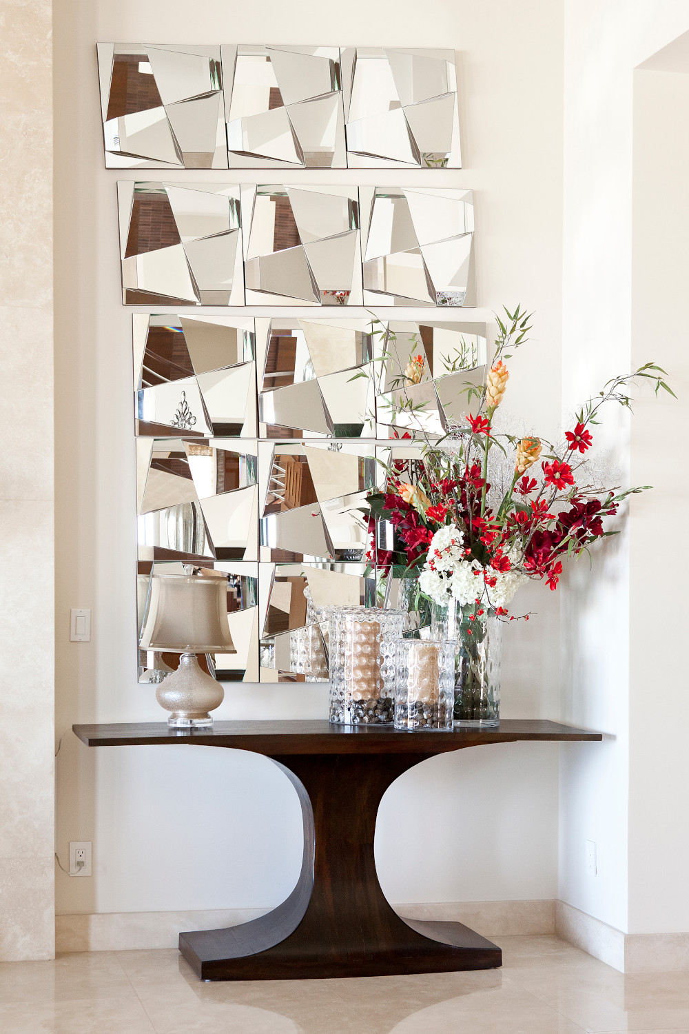 Modern custom home entry with stacked mirror squares, dark wood console table and glass vases.