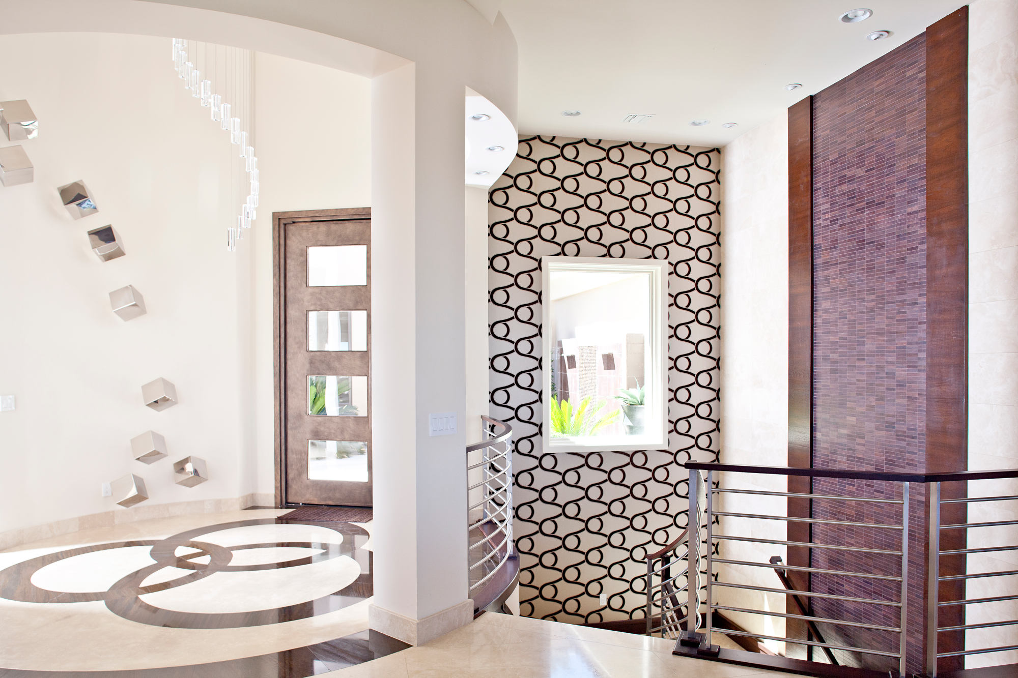 Modern custom home entry with pivotal front door, wallpaper, stone wall and modern crystal light.