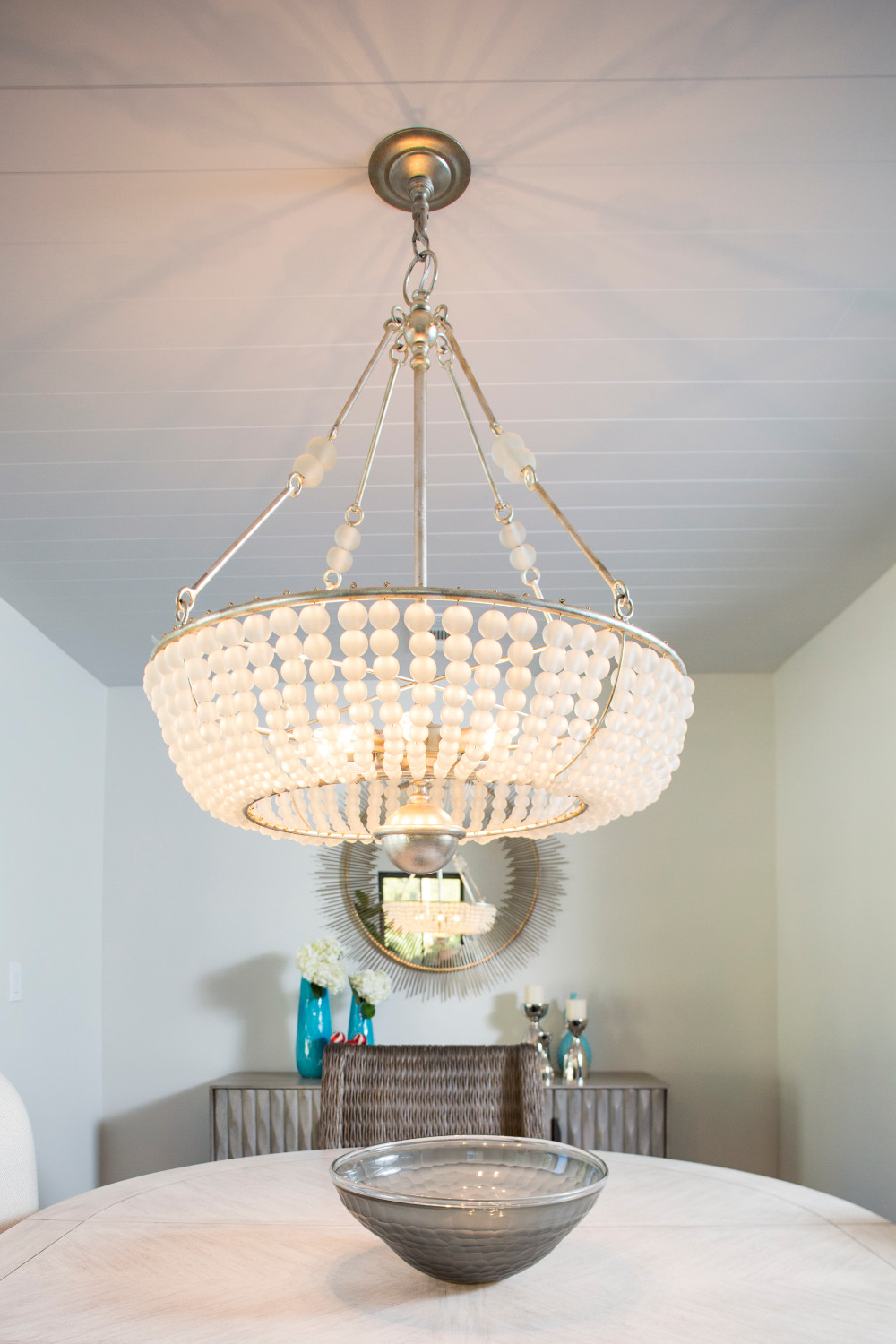 Dining room with white walls, galls white chandelier, shiplap ceiling and round gold wall mirror.