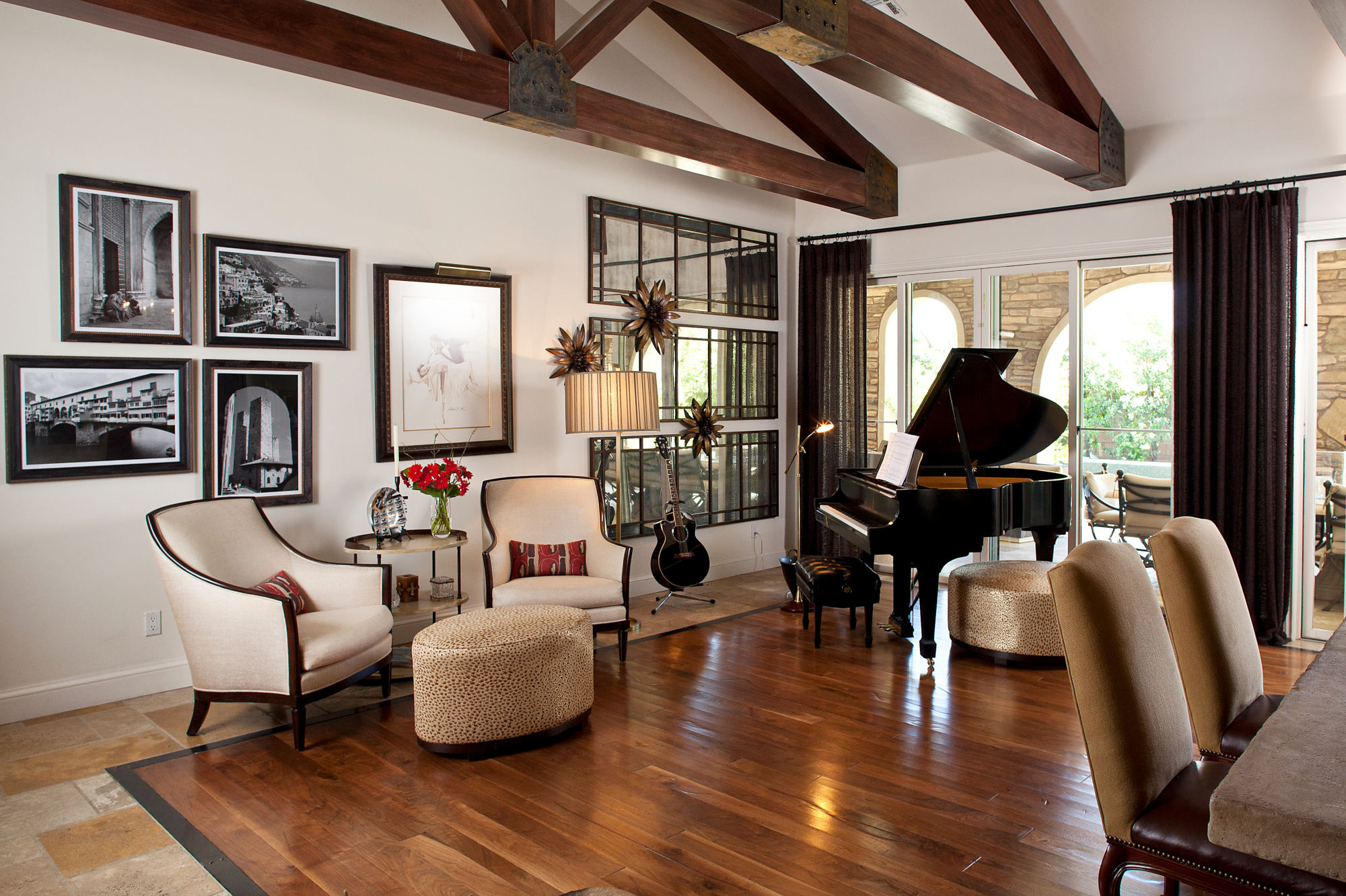 Spanish styled living room with wood ceiling trusses, wood flooring, white walls and black piano.