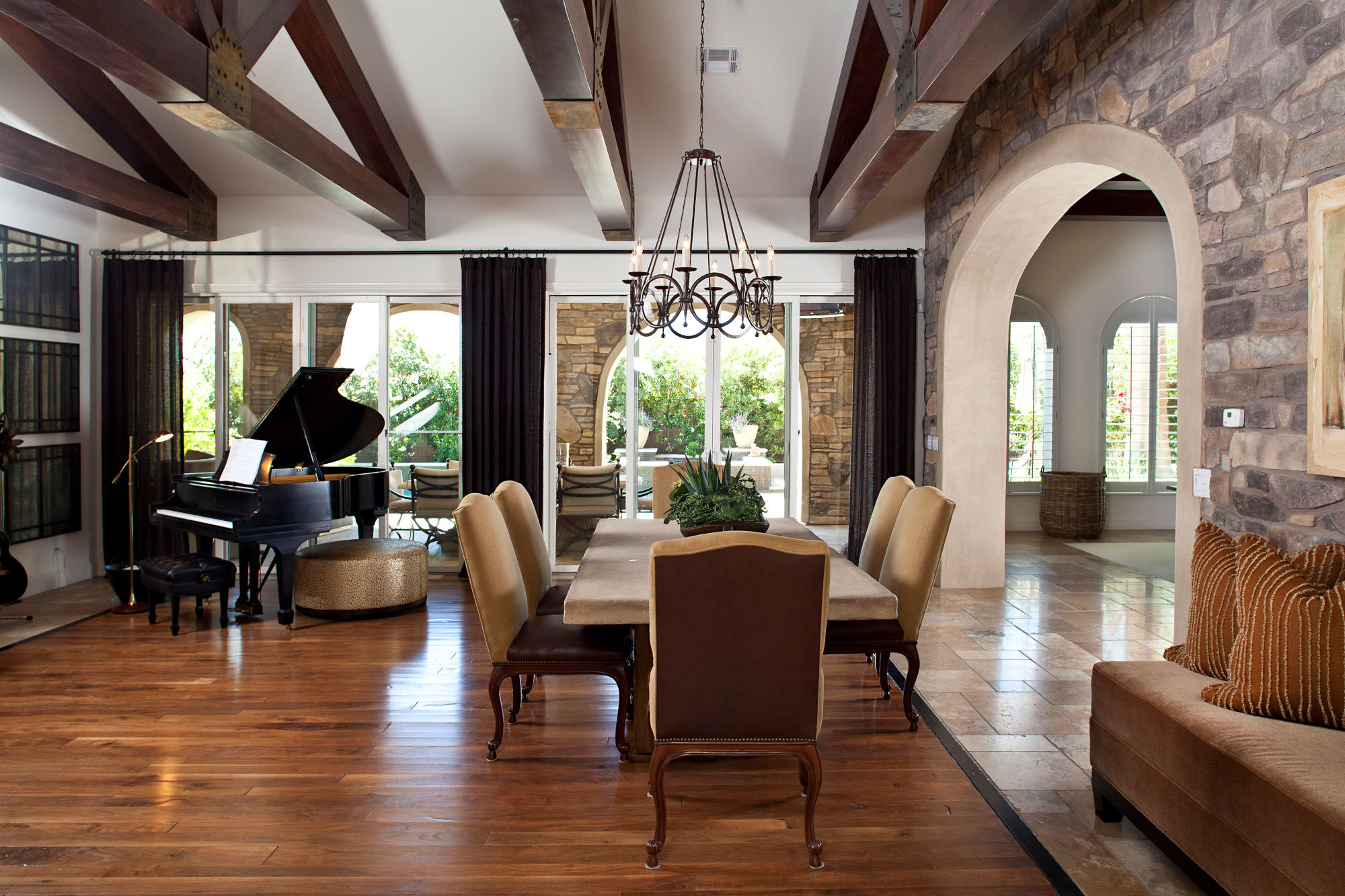 Spanish styled dining room with wood ceiling trusses, wood flooring, black wrought iron chandelier.