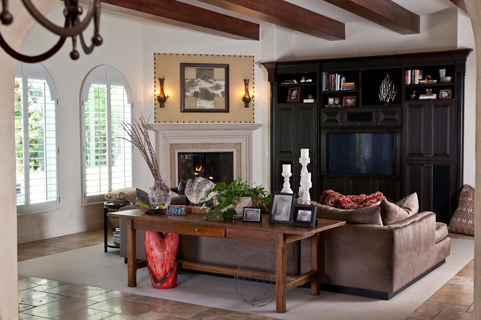 Spanish style family room with wood beams and custom stone fireplace.