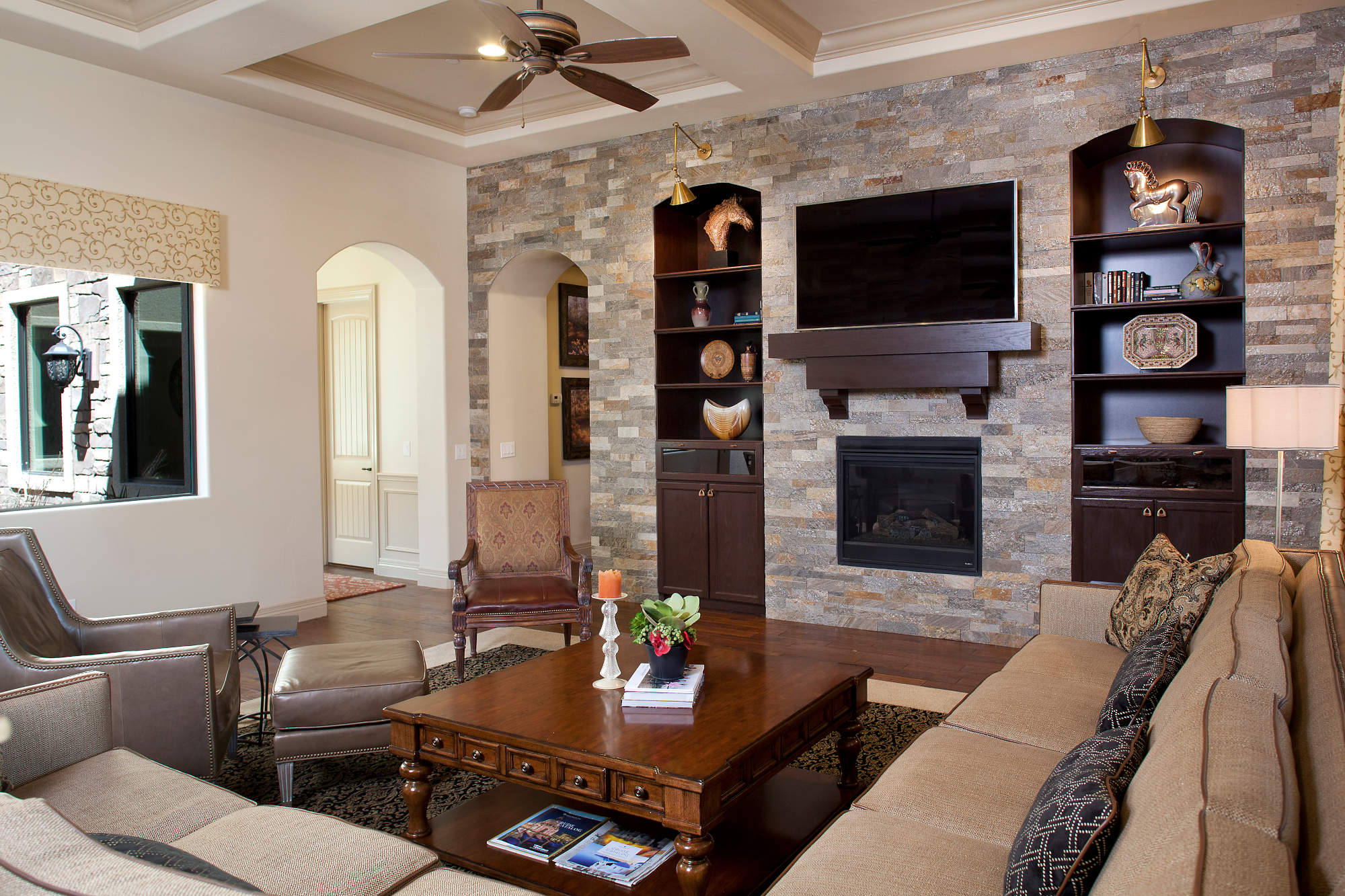 Traditional styled family room with stacked stone wall, fireplace and wood mantel.