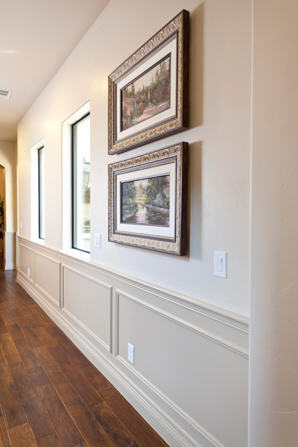 Home entry hallway with cream Wainscoting, wood flooring with landscape oil paintings on walls.