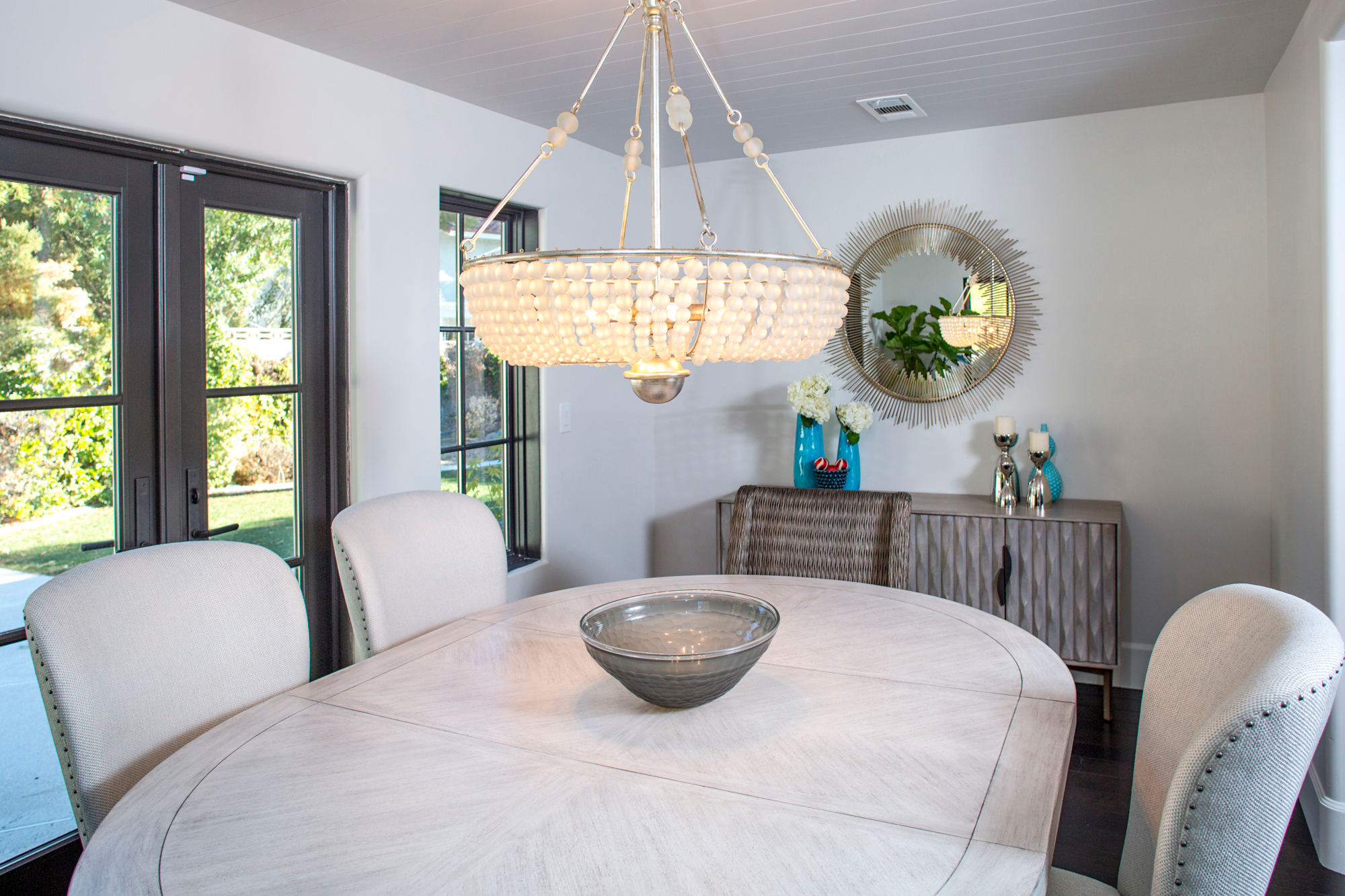 Dinning area, chandelier, shiplap ceiling with white wash wood table upholstered chairs.