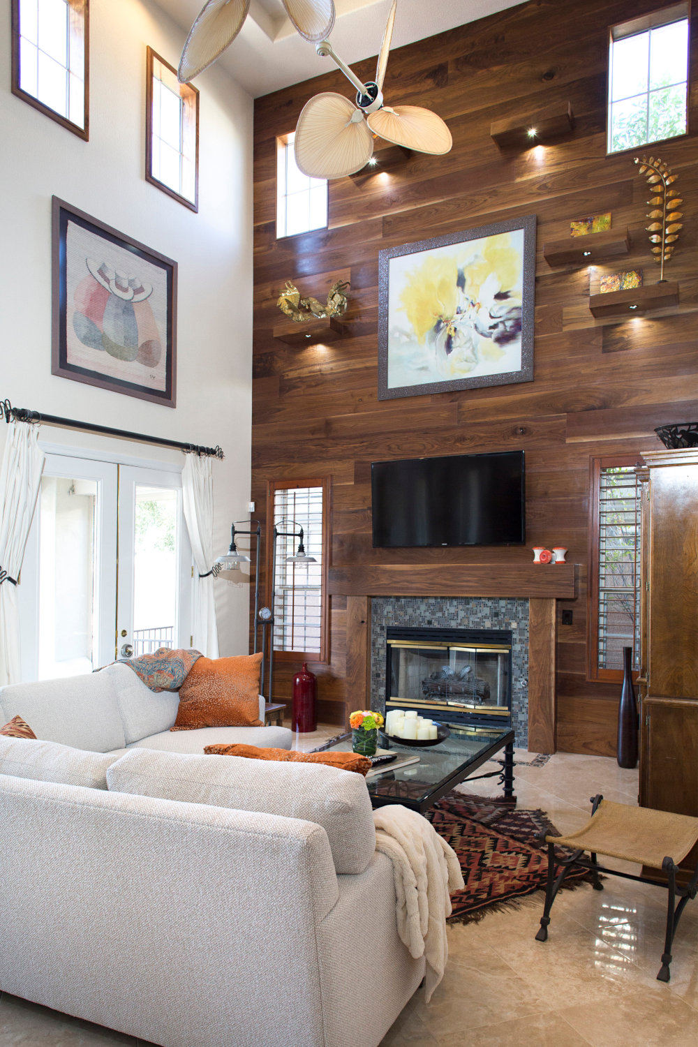 Family room with tall wood paneled wall and fireplace. White sectional setting.