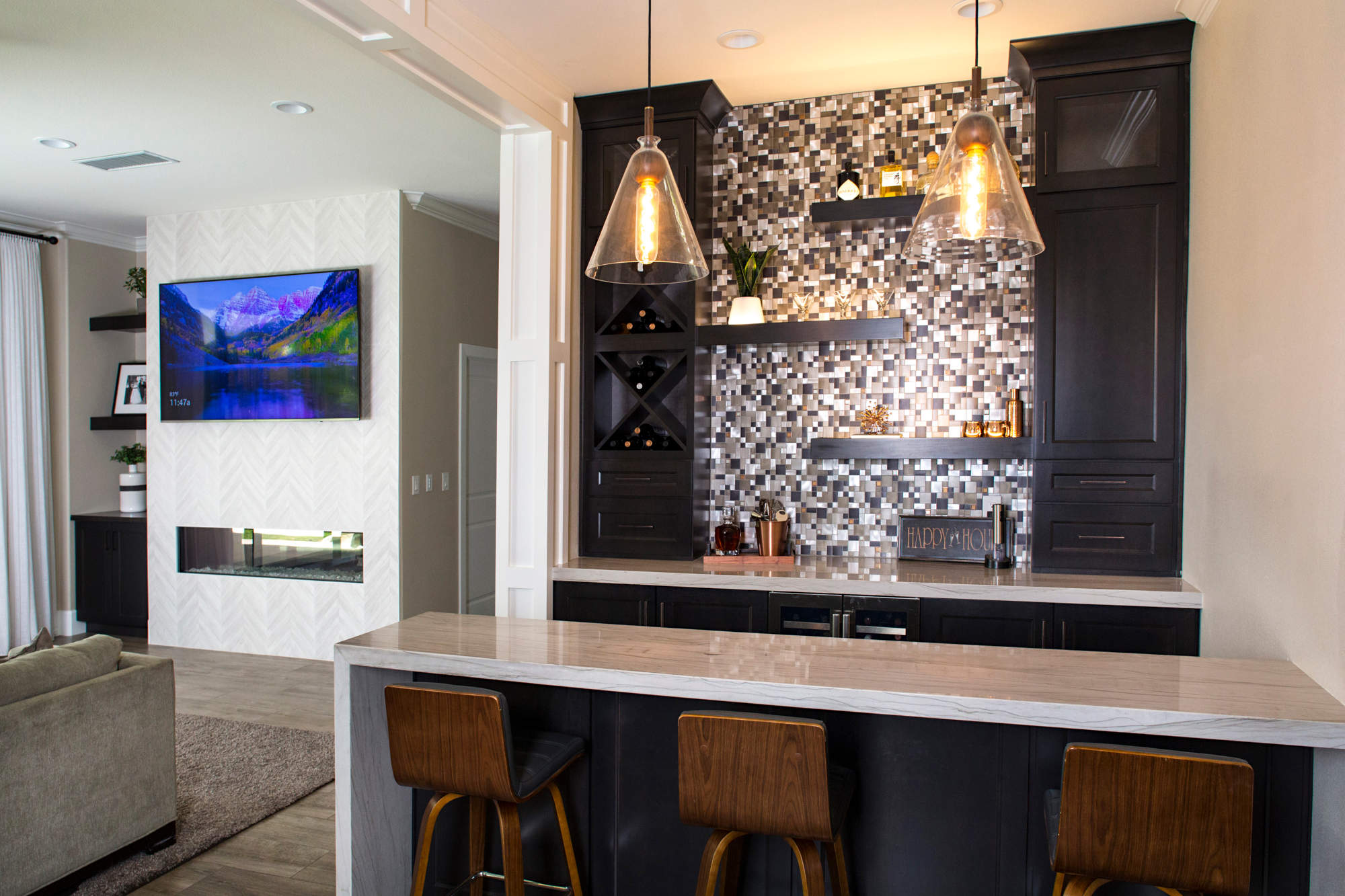 Family room with titled fireplace wall and bar section with barstools and pendent lighting.