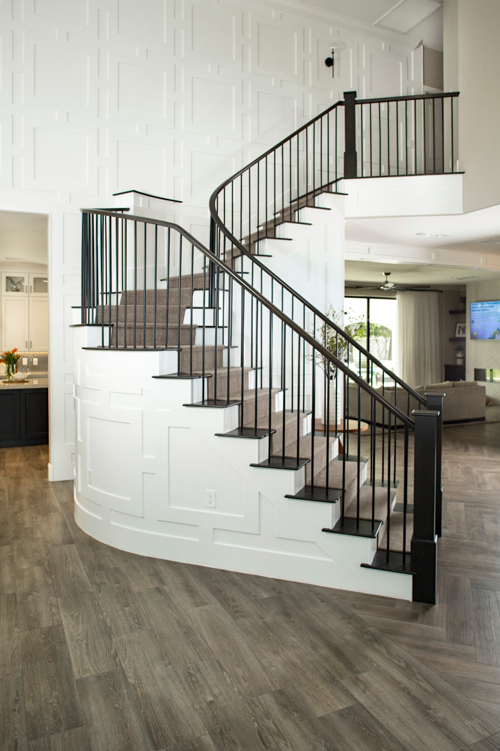Staircase and wall with white wood panelling, dark wood railing and dark wood stair steps.