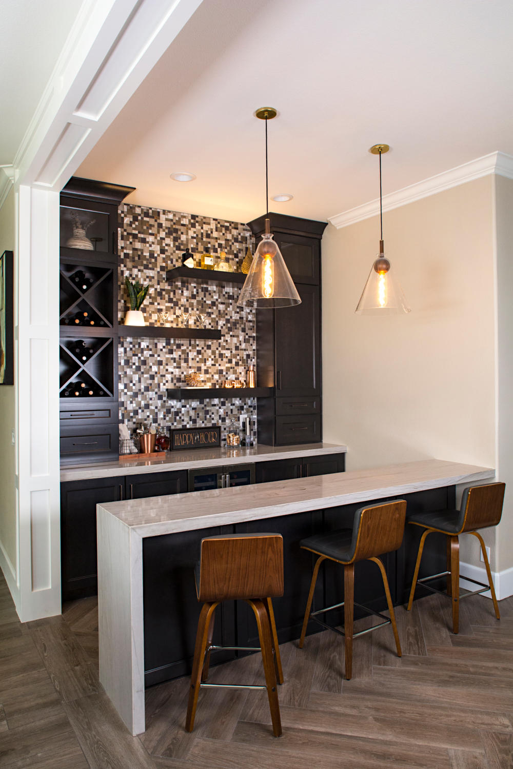 Home bar with barstools, natural stone bar top, pendent lights, dark cabinets.