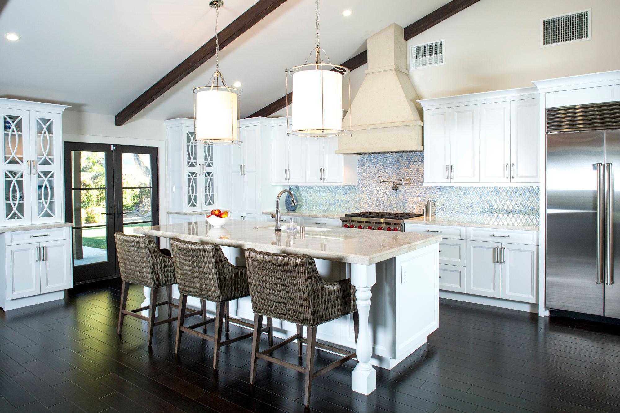 Santa Barbara styled white kitchen, mullion cabinets, large island with quartzite beige countertops.