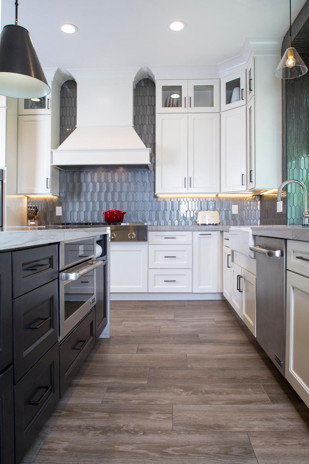 White kitchen with espresso island cabinet, metal cone shaped bronze pendent, wood wrapped hood.