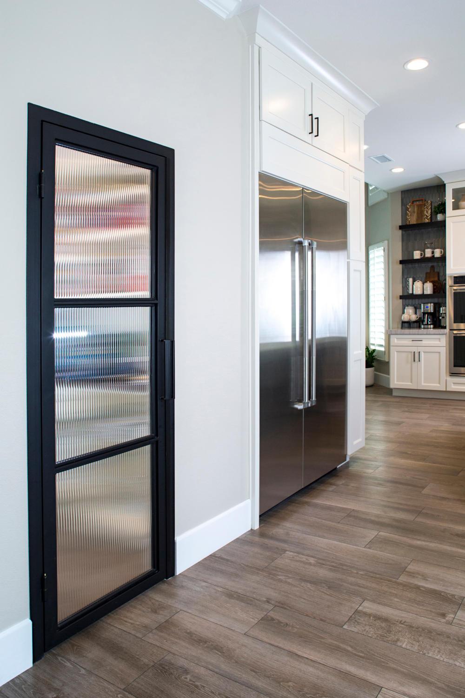 Black iron and reed glass pantry door next to Sub Zero refrigerator in white kitchen.