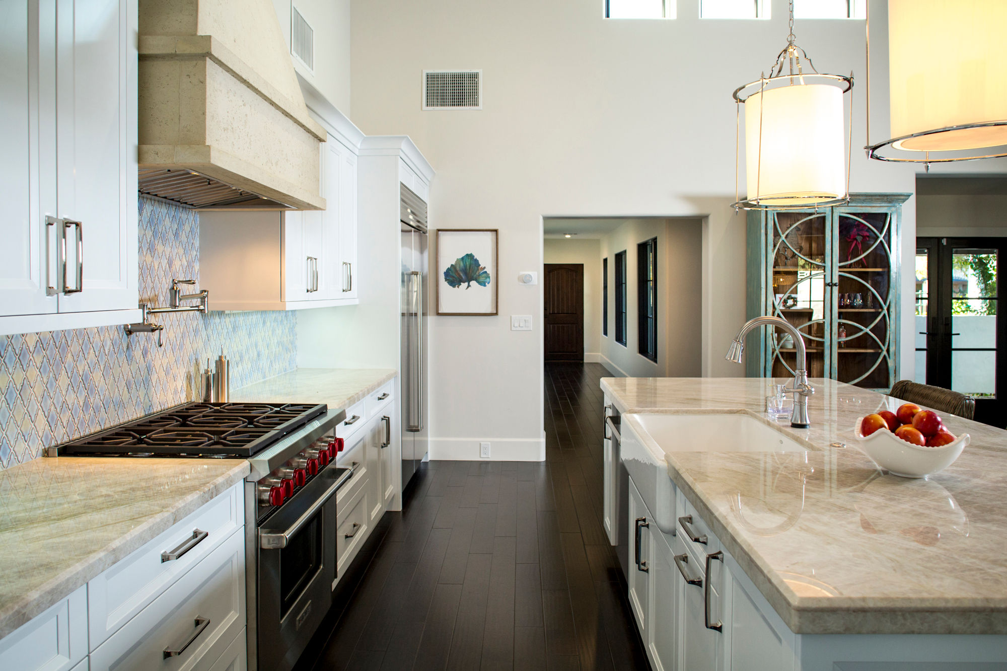 White Santa Barbara styled kitchen, stone stove hood, dark wood floors, large pendents over island.