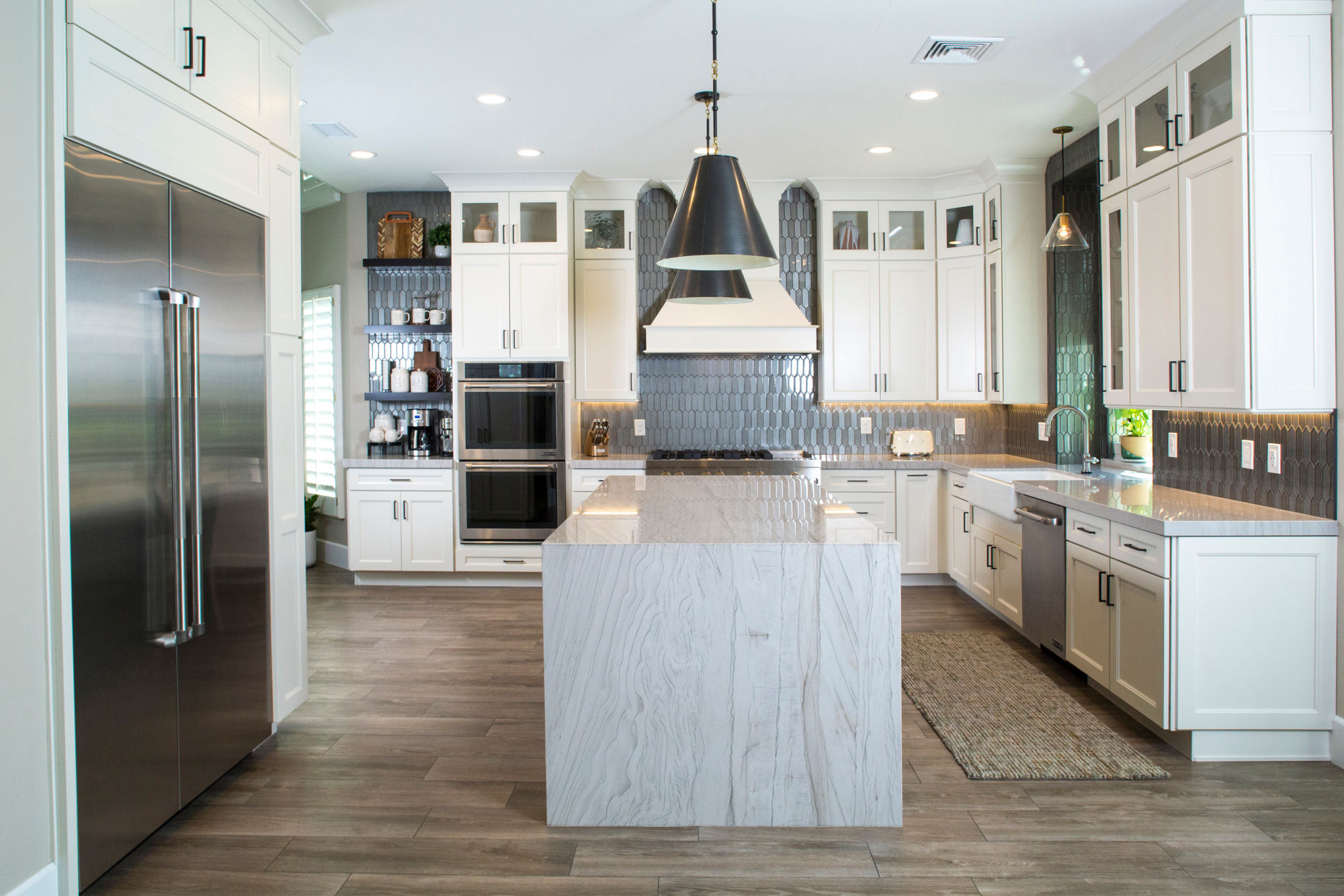 New white kitchen with stainless steel appliances and quartzsite waterfall island.
