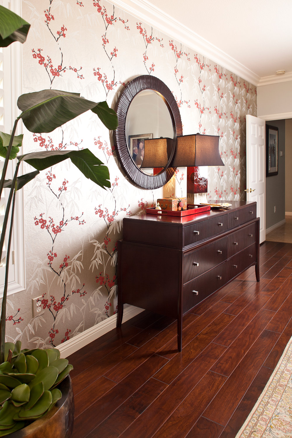 Master bedroom cherry blossom wallpaper, credence with round mirror, red table lamp and wood floor.