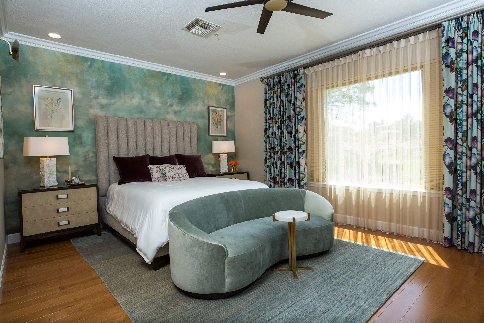 Master bedroom with sage wallpaper, multi colored drapes with sheers, wood floor, curved sofa.
