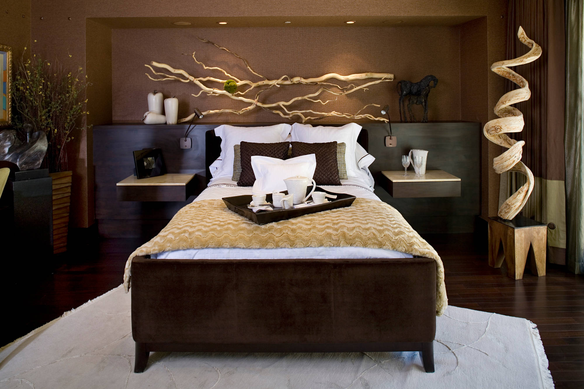 Contemporary bedroom with grass cloth wallpaper, organic wood sculpture and floating nightstands.