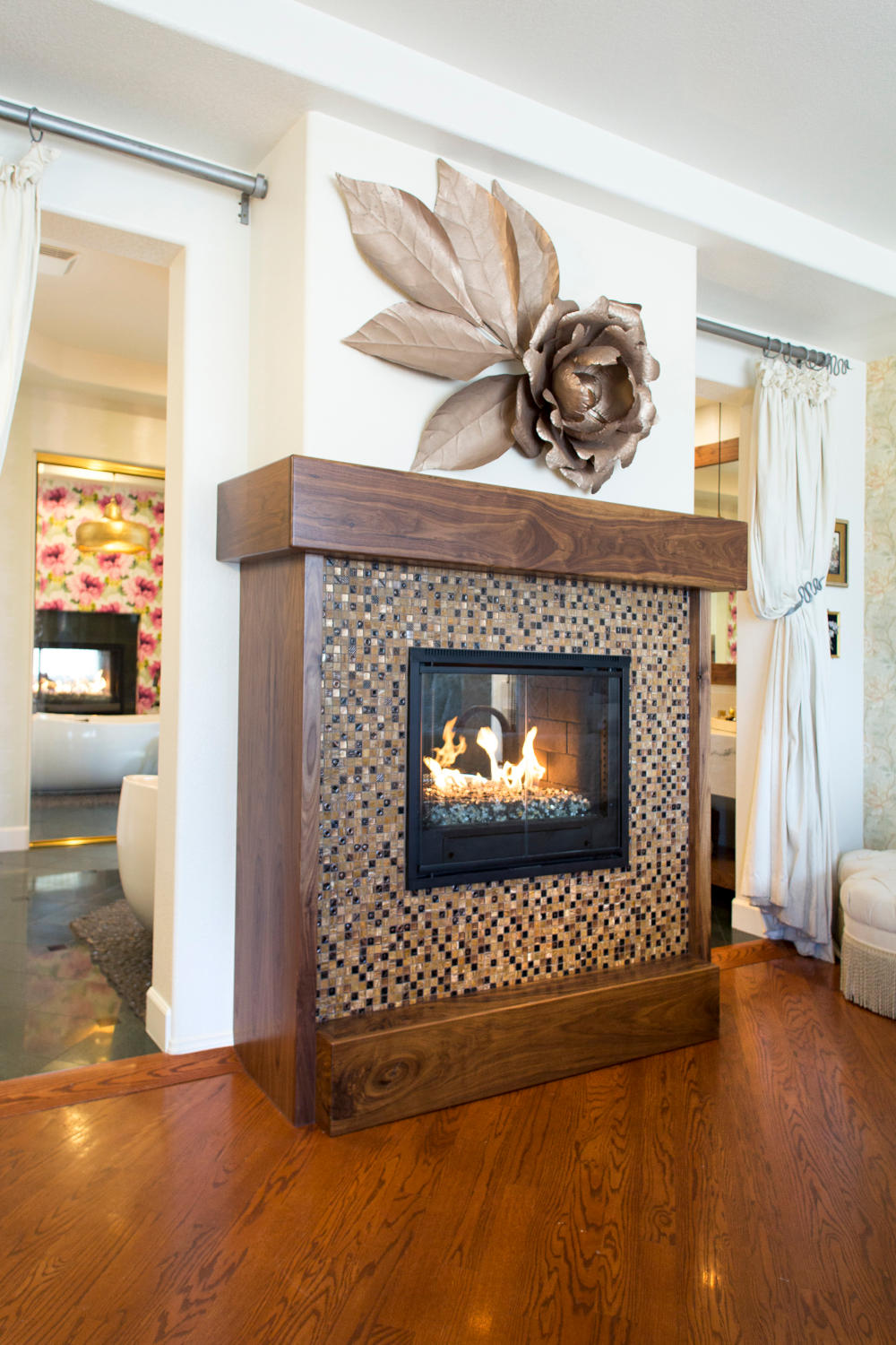 Master bedroom fireplace with wood mantel, mosaic tile suround and metal flower decor above.