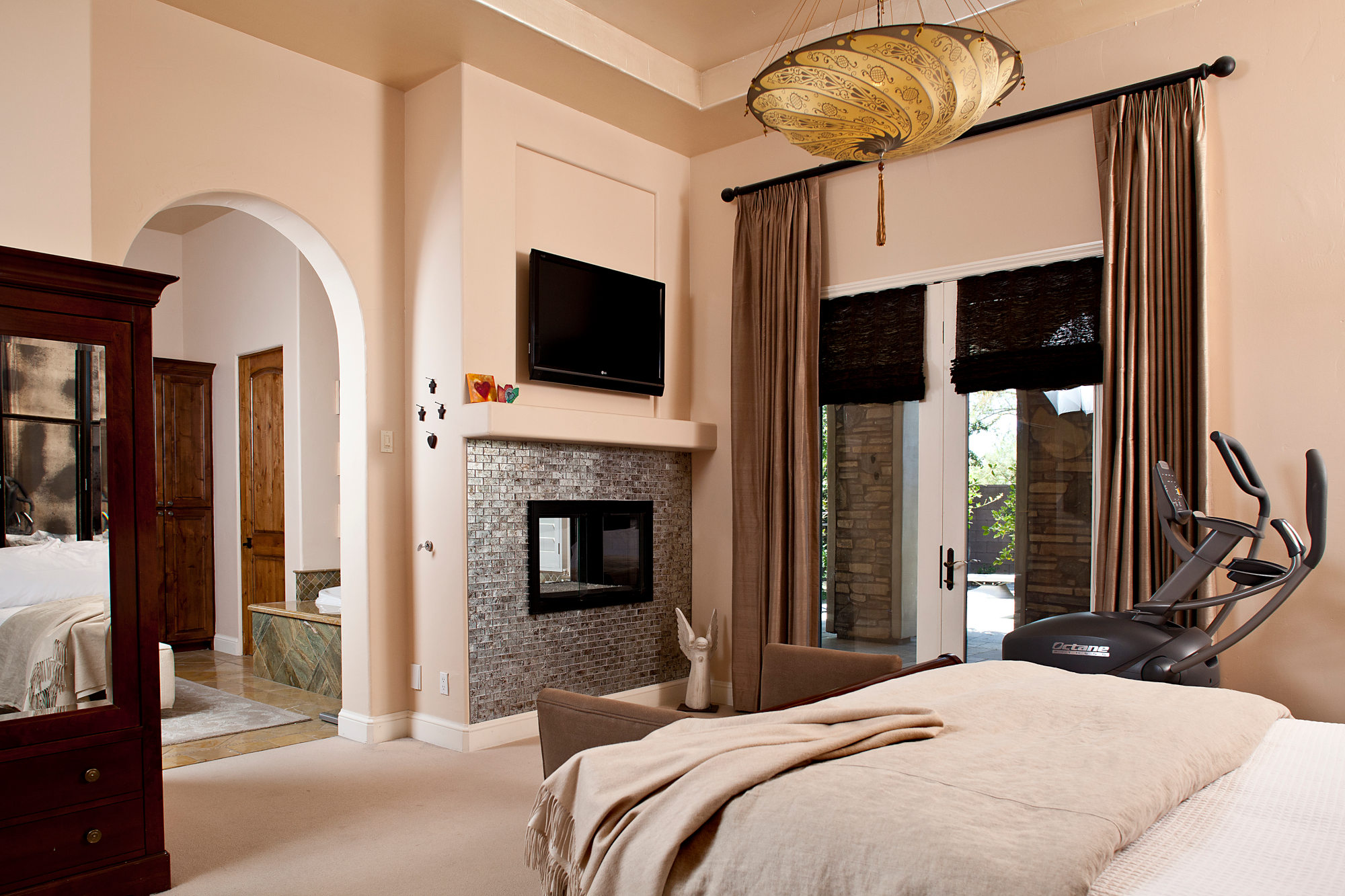Spanish styled master bedroom with fireplace and large french doors to the garden.