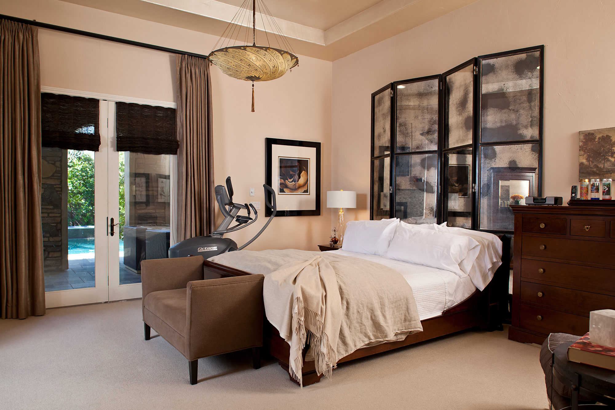 Spanish styled master bedroom with antique mirror headboard screen.