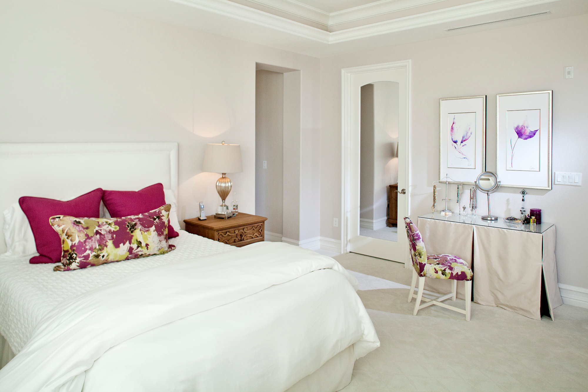 Bright white master bedroom fascia pillows and chair with crown molding and make up table.