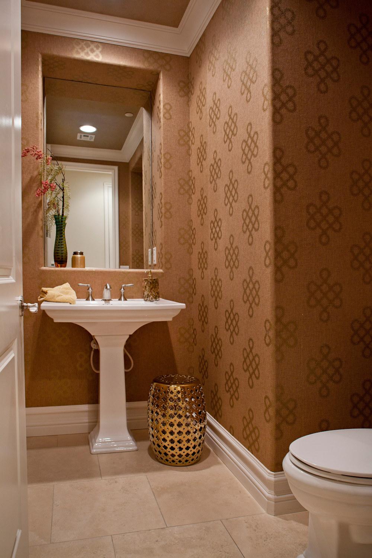 Copper grass cloth wallpaper powder bath with white pedestal sink and recessed mirror.