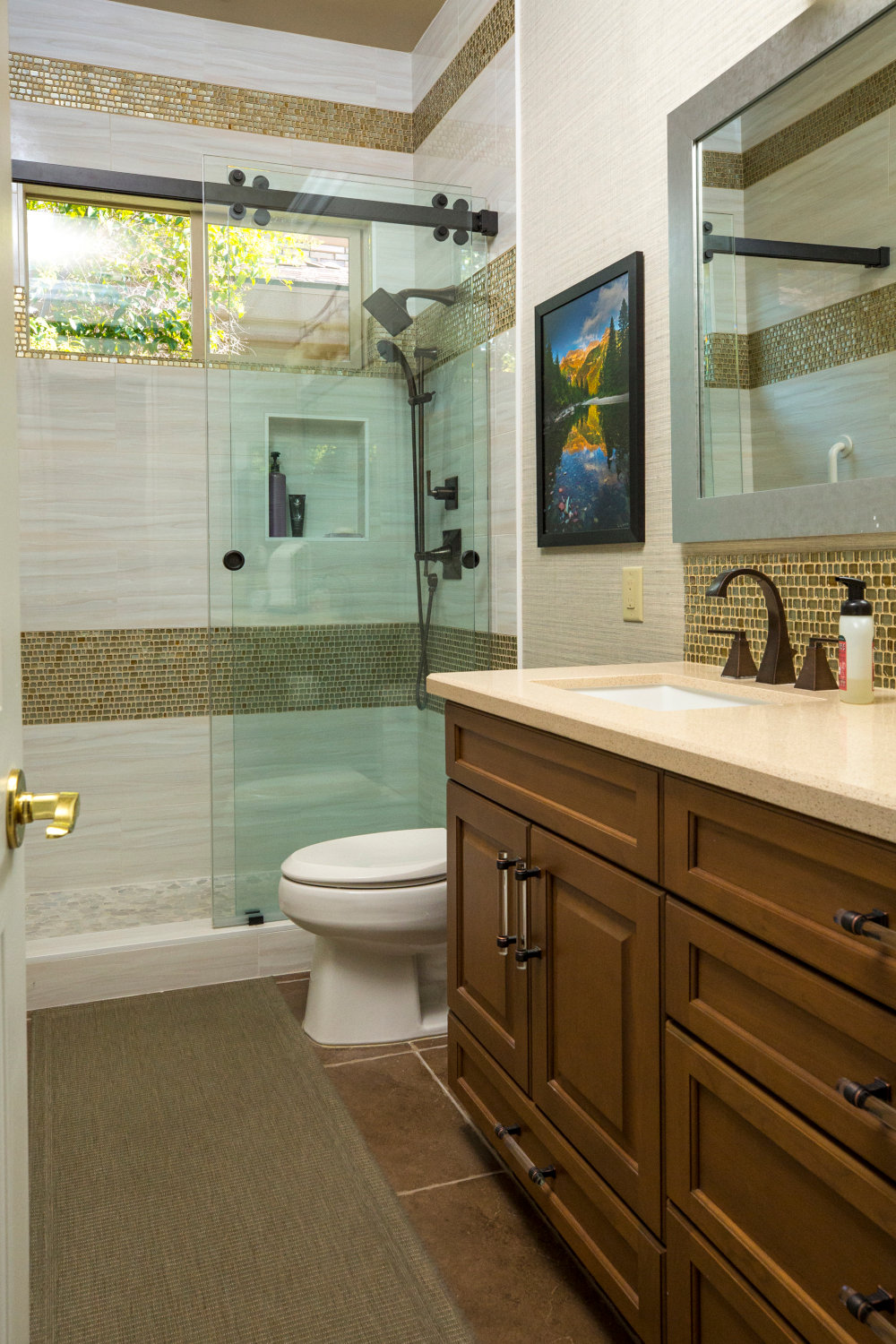Walk-in shower bath with gold backsplash, light wood vanity, oil rubbed bronze accents.