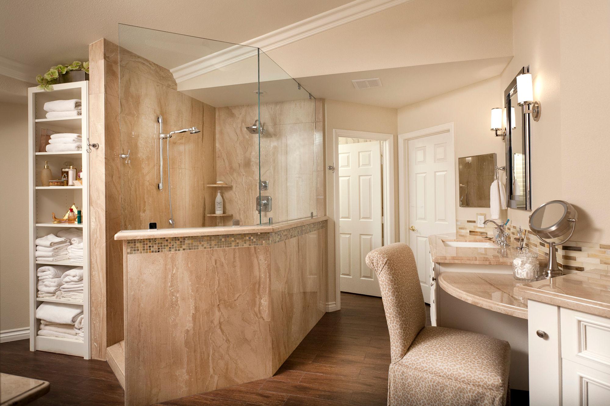 Marble slab walk-in master bath shower, built-in white wood linen cabinet and wood tile flooring.