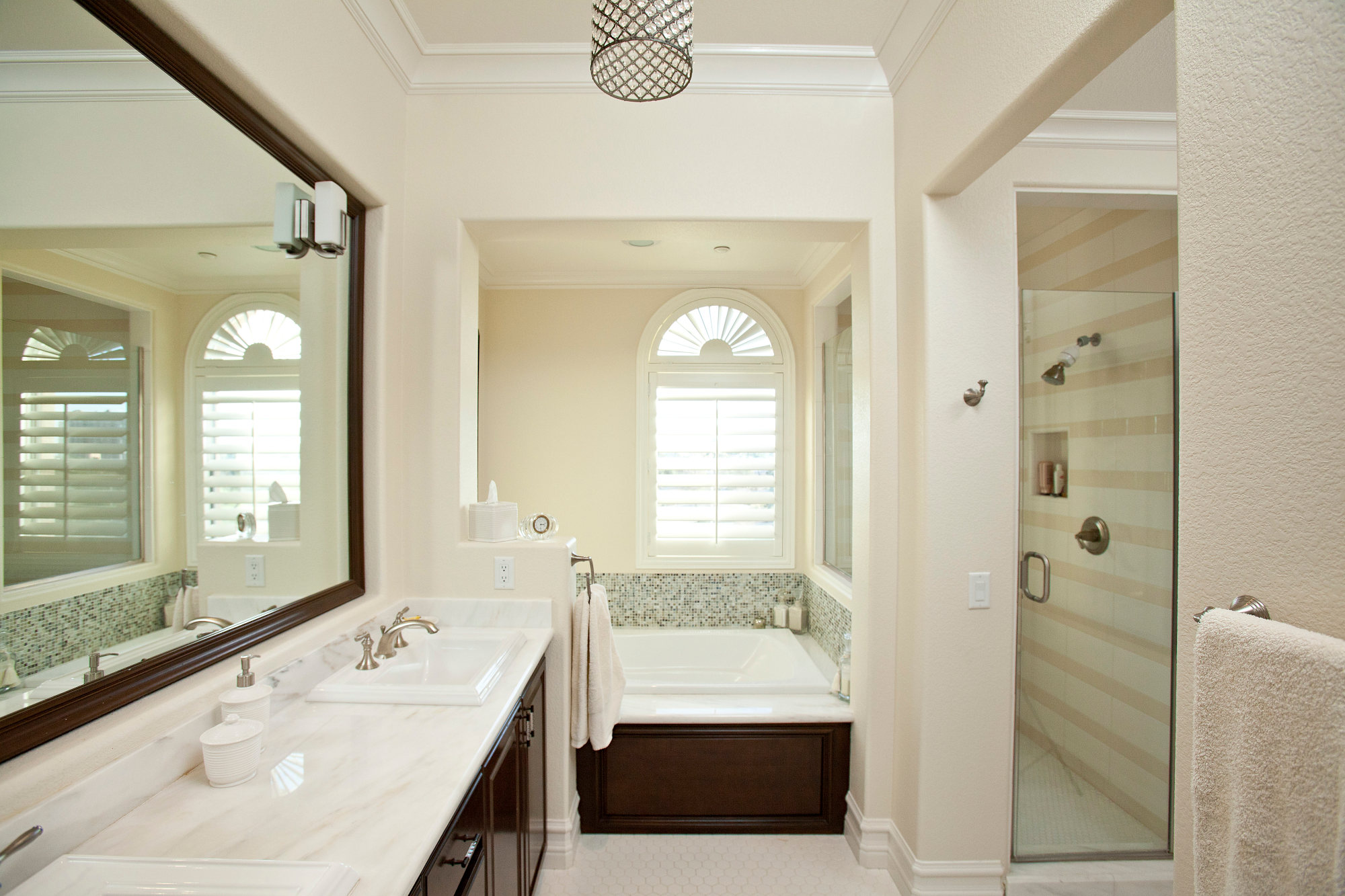 Spa inspired master bath with marble counters, neutral colors with large walk-in shower.