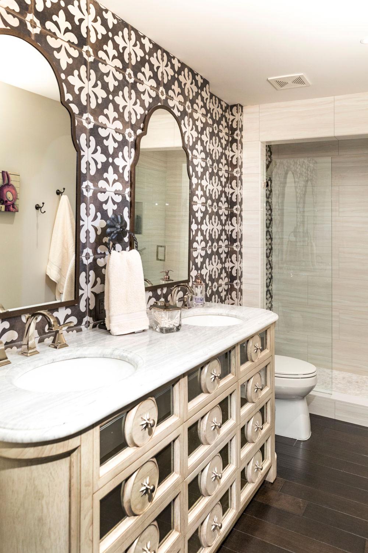 Bathroom with spanish tiled back wall, custom wood 2 sink vanity with marble top, dark wood floors.