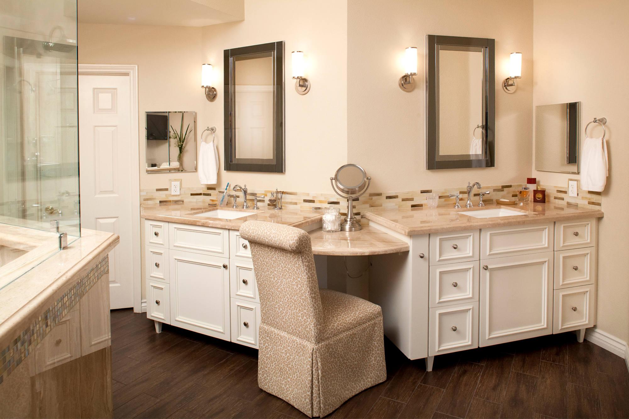 Traditional master bath with white vanities, marble countertops, glass backsplash, wood tile floor.