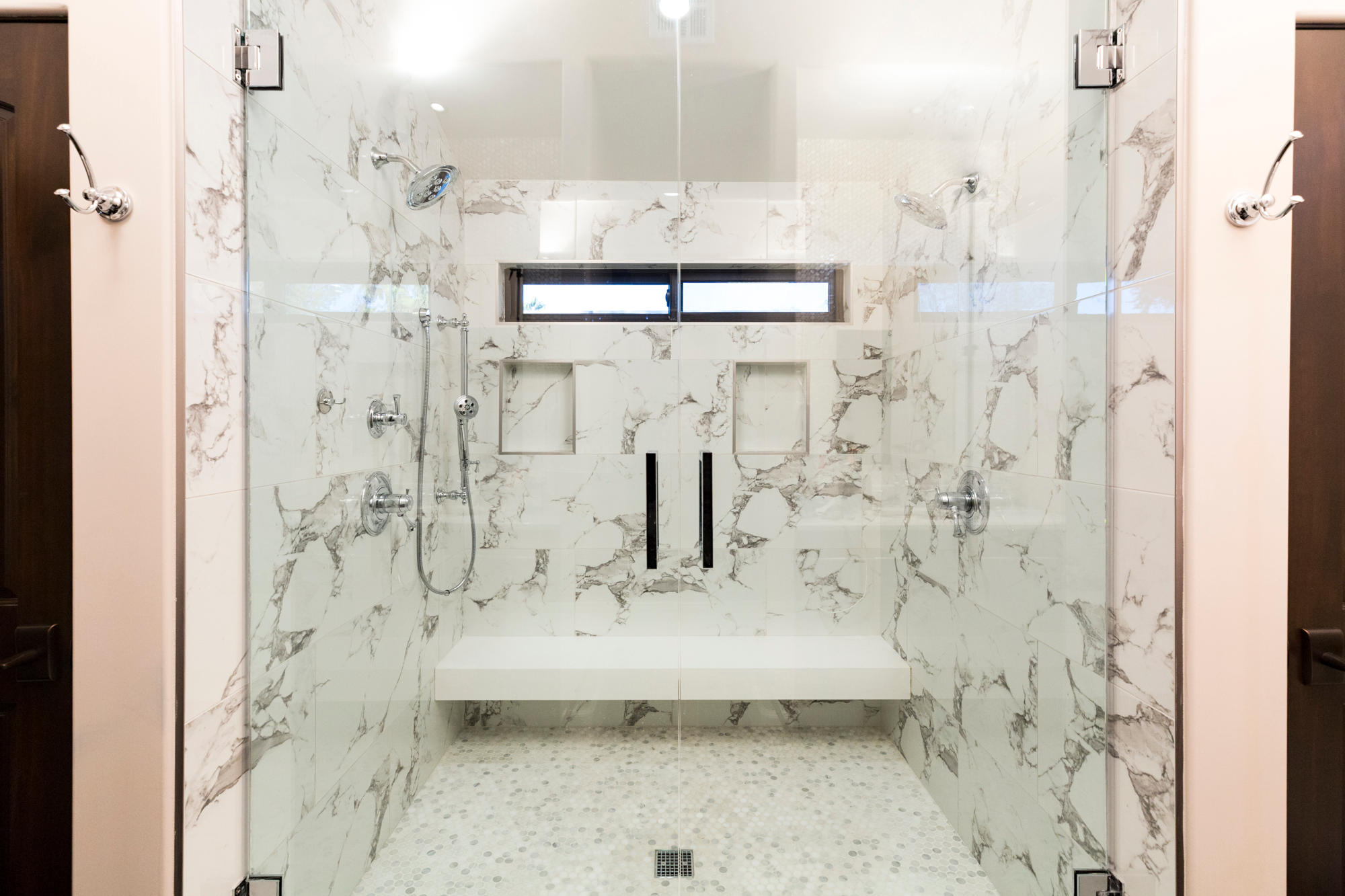 Master bath walk-in shower with white marble and chrome accents.