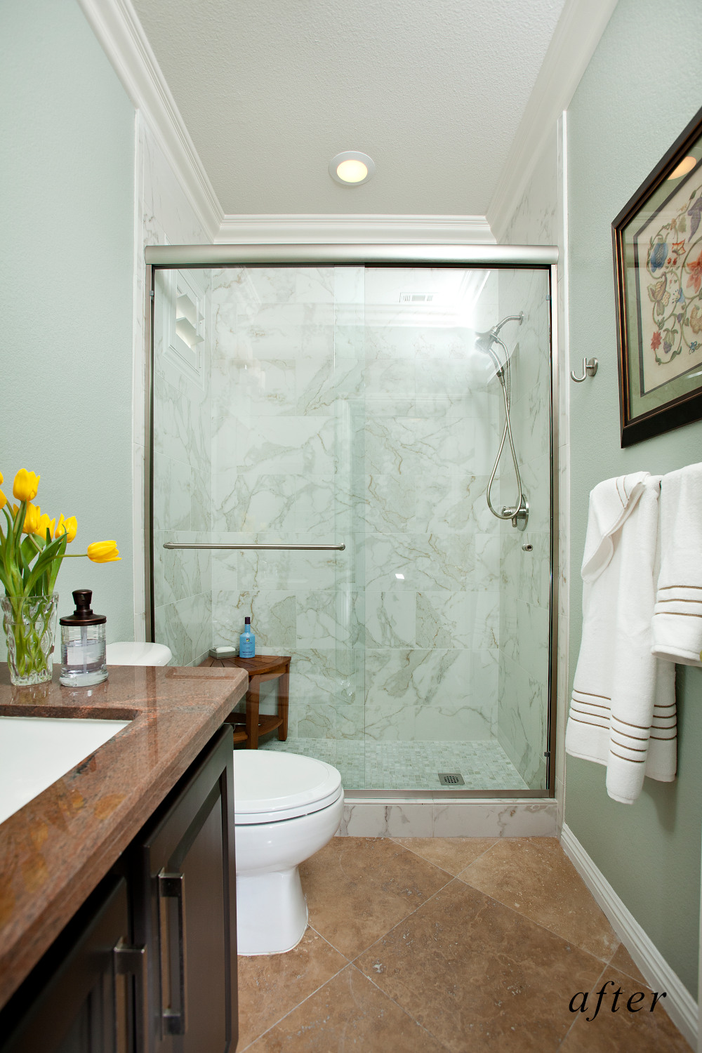 After remodel image: new bathroom, walk-in shower, light green colored  marble, new vanity and top.