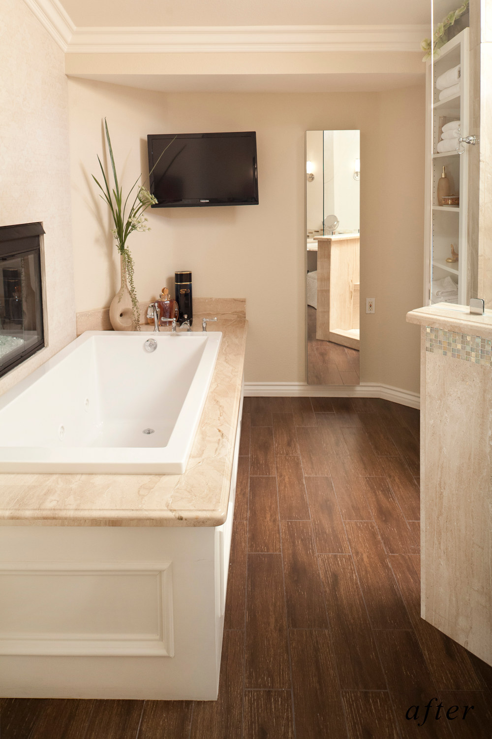 After remodel image: new master bath with brown marble, beige colored walls, brown tile floor.