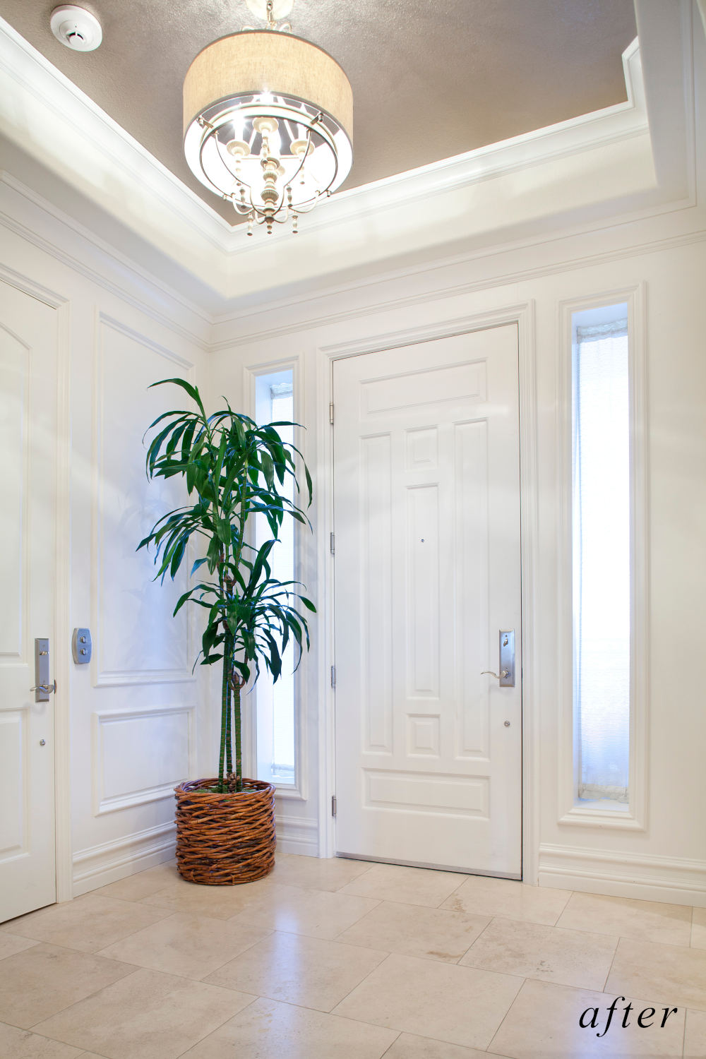 After remodel image: newly remodeled home entrance with white wood molding and wood paneling.