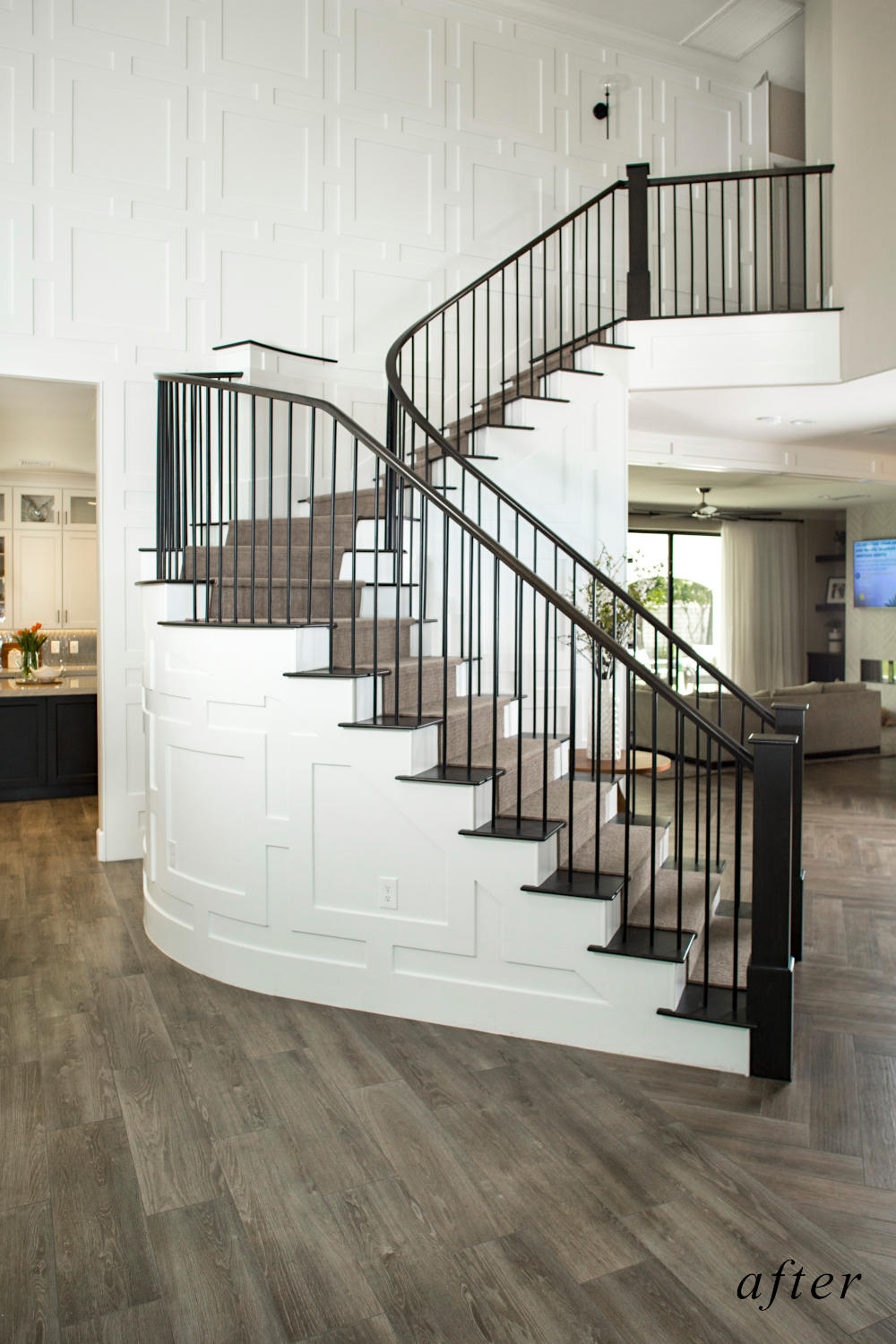 After remodel image: New home staircase with white wood paneling black wood handrails and steps.