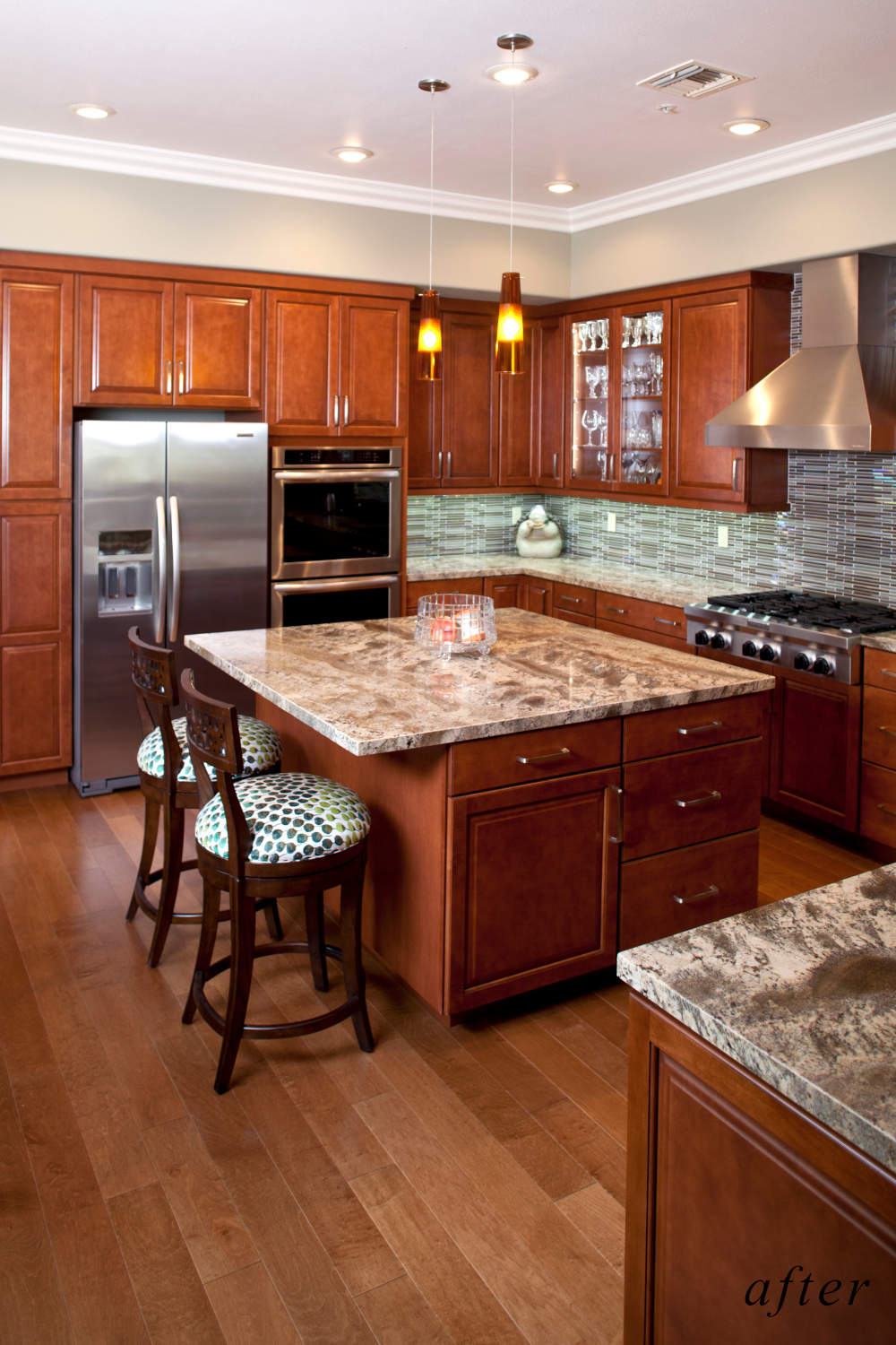 After remodel image: New kitchen with cherry colored cabinets, marble counters, dark wood floor.