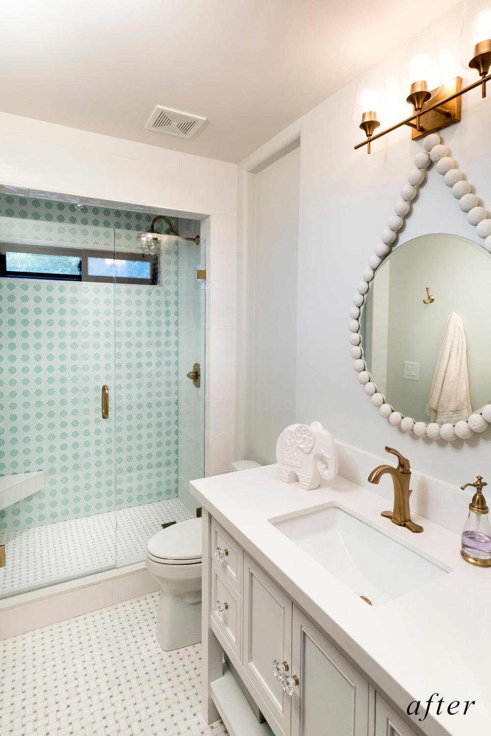 After remodel image: beautiful white marble themed bathroom with walk-in shower with gold accents.