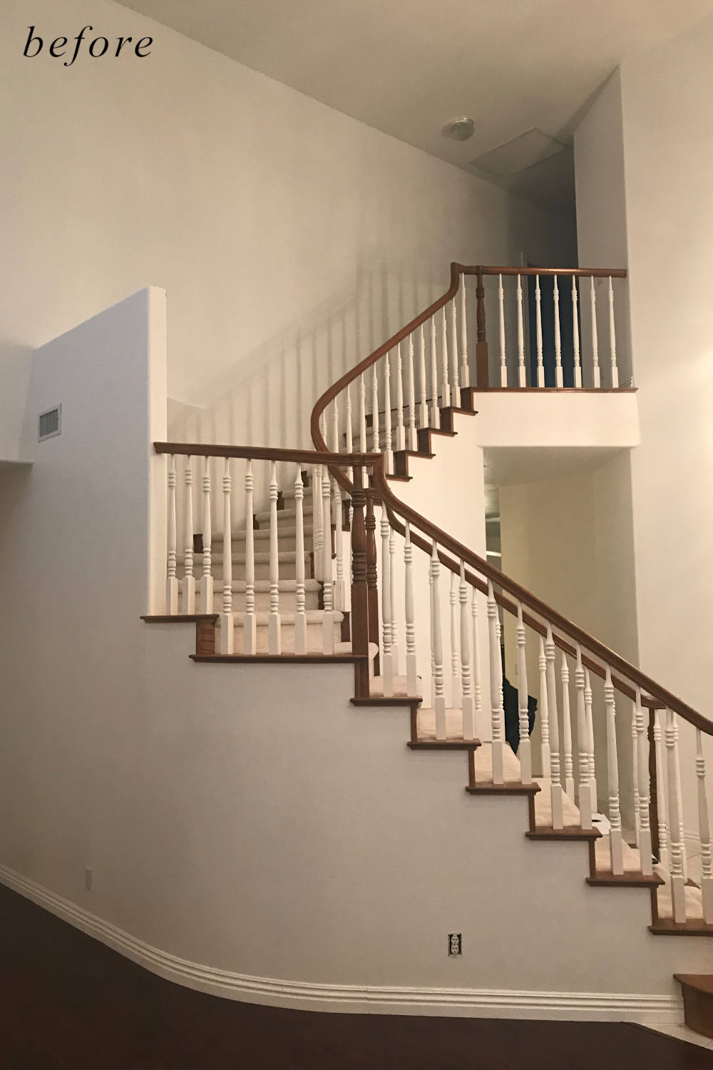 Before remodel image: dated and standard home staircase with old carpet and basic railing.