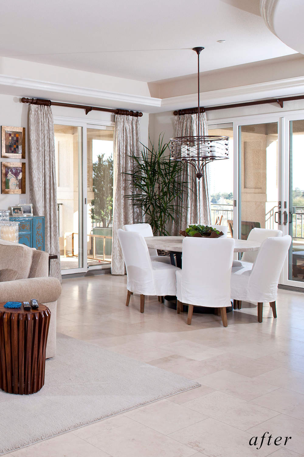 After remodel image: bright home dining room with stone top dining table, white dining chairs.