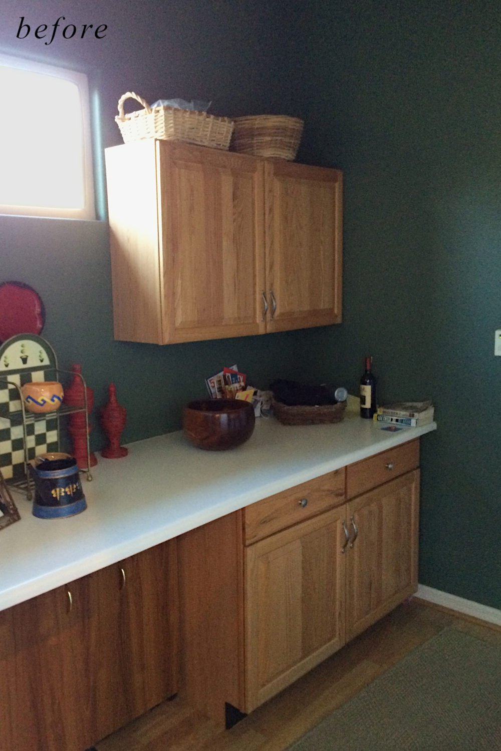 Before remodel image: old and dated laundry room with basic small cabinets.