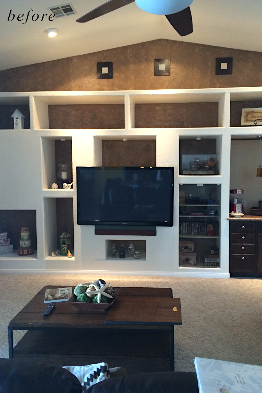 Before remodel image: basic and dated home entertainment wall in family room.